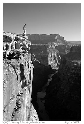 Man standing at  edge of  Grand Canyon at Toroweap, early morning. Grand Canyon National Park (black and white)