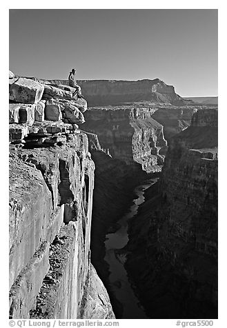 Visitor sitting on  edge of  Grand Canyon, Toroweap. Grand Canyon National Park (black and white)