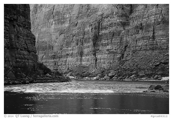 Glassy river and rapids below Redwall limestone canyon walls. Grand Canyon National Park (black and white)