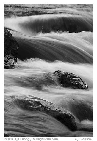 Boulders and rapids with warm light from canyon walls reflected. Grand Canyon National Park (black and white)