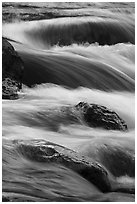Boulders and rapids with warm light from canyon walls reflected. Grand Canyon National Park ( black and white)
