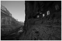 Ancient Nankoweap granaries with windows lit and Colorado River at dusk. Grand Canyon National Park ( black and white)