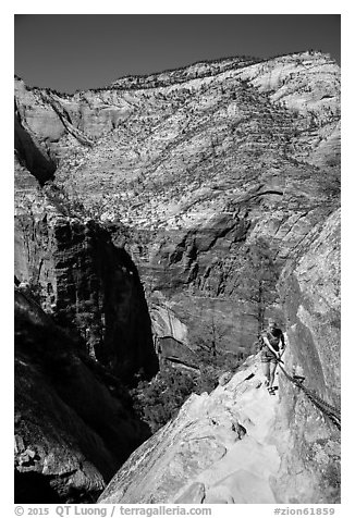 Woman hiker clinging to cable on Hidden Canyon trail. Zion National Park (black and white)