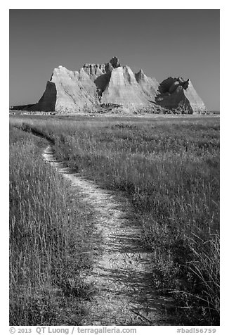 Trail winding in prairie next to butte. Badlands National Park (black and white)