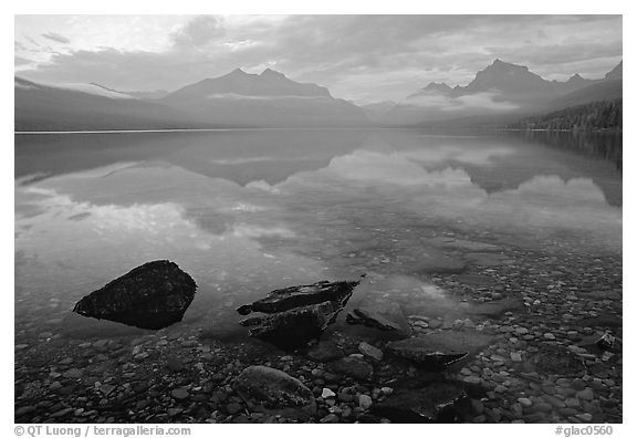 Rocks, peebles, and mountain reflections in lake McDonald. Glacier National Park (black and white)