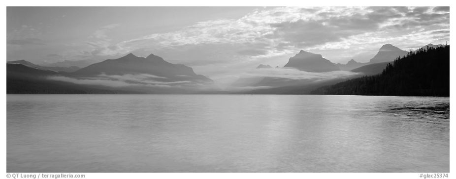 Serene lake with clouds hanging over mountains. Glacier National Park (black and white)