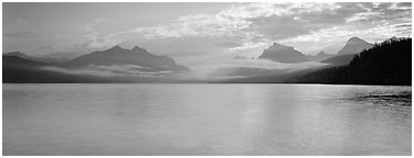 Serene lake with clouds hanging over mountains. Glacier National Park (Panoramic black and white)