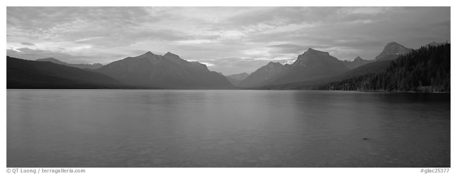 Mountains rising above calm lake in the evening. Glacier National Park (black and white)