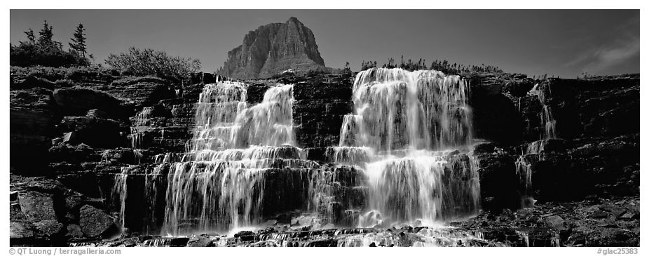 Waterfall flowing over dark rock and peak. Glacier National Park (black and white)