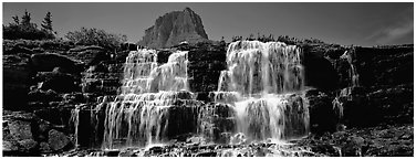 Waterfall flowing over dark rock and peak. Glacier National Park (Panoramic black and white)