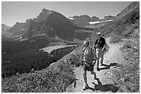 Couple hiking on trail, with Grinnell Lake below. Glacier National Park, Montana, USA. (black and white)