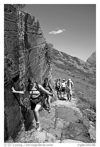 Walking under a small waterfall on the Grinnell Glacier trail. Glacier National Park (black and white)