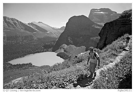 Hikers on trail overlooking Grinnell Lake. Glacier National Park (black and white)