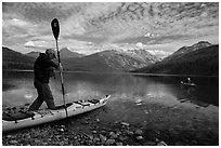 Kayaker steps into kayak, Kintla Lake. Glacier National Park ( black and white)