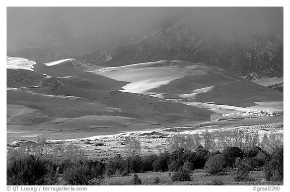 Storm light illuminates portions of the dune field. Great Sand Dunes National Park and Preserve (black and white)