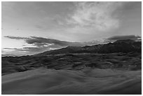 Dune field and Sangre de Cristo mountains with cloud lighted by sunset. Great Sand Dunes National Park, Colorado, USA. (black and white)