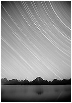 Star trails on Teton range above Jackson lake, dusk. Grand Teton National Park, Wyoming, USA. (black and white)