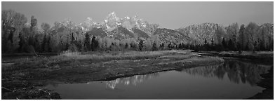 Jagged mountains and autumn colors reflected at sunrise. Grand Teton National Park (Panoramic black and white)