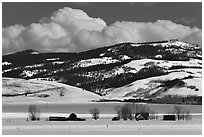 Distant row of barns, hills and clouds in winter. Grand Teton National Park, Wyoming, USA. (black and white)