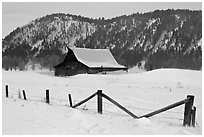 Fence and historic Moulton Barn in winter. Grand Teton National Park, Wyoming, USA. (black and white)