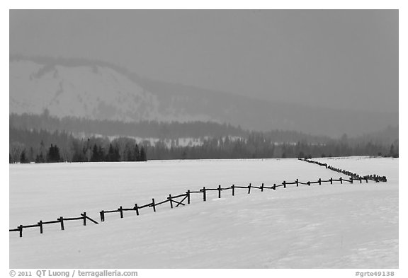 Wooden fence, snow-covered flat, hills in winter. Grand Teton National Park (black and white)