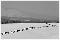 Wooden fence, snow-covered flat, hills in winter. Grand Teton National Park, Wyoming, USA. (black and white)