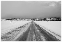 Road in winter at dusk, Gross Ventre valley. Grand Teton National Park, Wyoming, USA. (black and white)