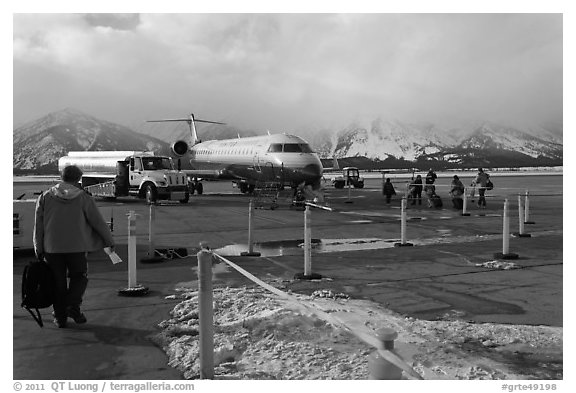 Passengers walking towards plane on Jackson Hole Airport. Grand Teton National Park (black and white)