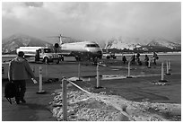 Passengers walking towards plane on Jackson Hole Airport. Grand Teton National Park, Wyoming, USA. (black and white)