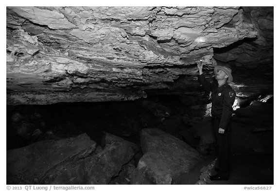 Ranger pointing at speleotherm in large cave room. Wind Cave National Park (black and white)