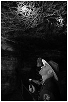 Ranger pointing flashlight at boxwork. Wind Cave National Park ( black and white)