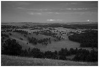 Rolling hills with distant lightening storm at dusk. Wind Cave National Park, South Dakota, USA. (black and white)