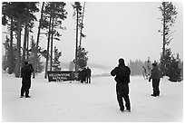 Tourists take pictures with entrance sign in winter. Yellowstone National Park, Wyoming, USA. (black and white)