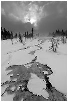 Colorful thermal stream and dark clouds, winter. Yellowstone National Park, Wyoming, USA. (black and white)