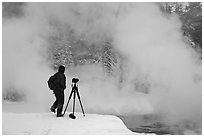 Photographer standing next to hot springs. Yellowstone National Park, Wyoming, USA. (black and white)