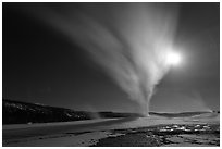 Old Faithful Geyser erupts at night. Yellowstone National Park, Wyoming, USA. (black and white)