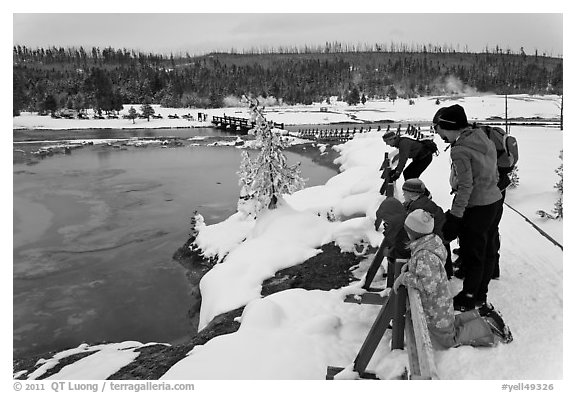 Family looks at thermal pool in winter. Yellowstone National Park, Wyoming, USA.