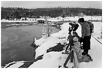 Family looks at thermal pool in winter. Yellowstone National Park, Wyoming, USA. (black and white)