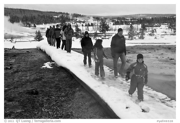 Tourists walk over snow-covered boardwalk. Yellowstone National Park (black and white)