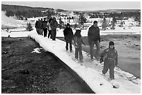 Visitors walk over snow-covered boardwalk. Yellowstone National Park, Wyoming, USA. (black and white)