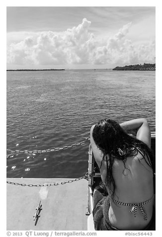 Woman relaxes on snorkeling boat as it enters Caesar Creek. Biscayne National Park (black and white)