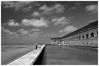 Tourists stroll on the seawall. Dry Tortugas National Park, Florida, USA. (black and white)