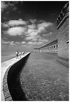 Tourists walking on seawall. Dry Tortugas National Park, Florida, USA. (black and white)