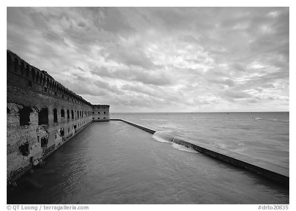 Fort Jefferson brick rampart and moat with wave over seawall, cloudy weather. Dry Tortugas National Park (black and white)