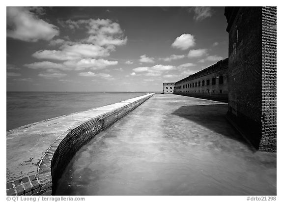 Moat with turquoise waters, seawall, and fort. Dry Tortugas National Park (black and white)