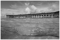Split view of Fort Jefferson and water with fish. Dry Tortugas National Park, Florida, USA. (black and white)