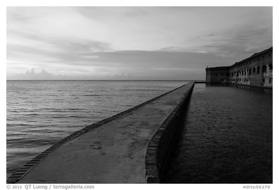 Fort Jefferson moat and walls at sunset with tourists in distance. Dry Tortugas National Park (black and white)
