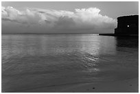 Tropical clouds, beach, and fort at sunrise. Dry Tortugas National Park, Florida, USA. (black and white)