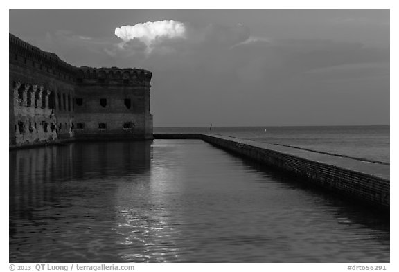 Moat, fort, bright cloud at dawn. Dry Tortugas National Park (black and white)