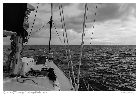 Loggerhead lighthouse seen from sailboat under dark skies. Dry Tortugas National Park (black and white)